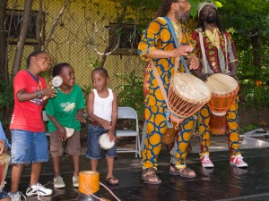 Exuberant young drummers getting their groove on next to the real drummers accompanying dancers at the African Dance Fest.