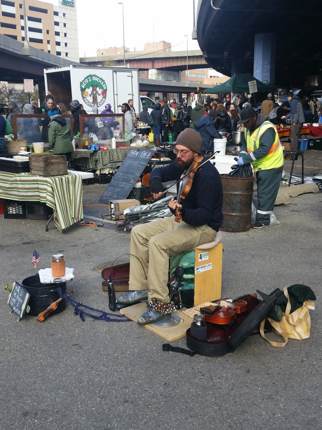 A one-man band plays lively bluegrass and creates a musical space in the Baltimore Farmer's market.