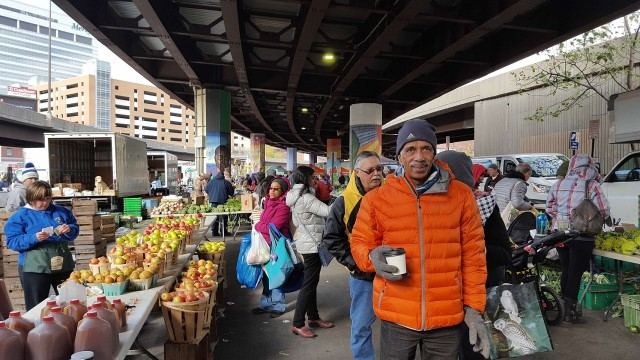 Farmer's market shopping with an organic warm coffee in hand, under the roof made by the elevated highway through the city.