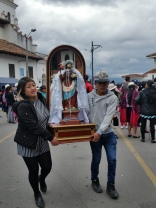 Catholic saints and other religious icons being carried into the Catholic church plaza by indigenous Ecuadorians
